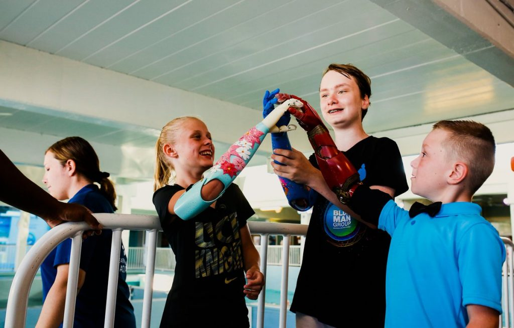 Personalized and 3D printed bionic arms for children. Photo via Limbitless Solutions/Adobe
