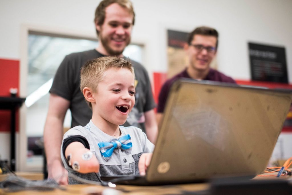 One child trying out Limbitless Solutions bionic arm model. Photo via Limbitless Solutions/Adobe