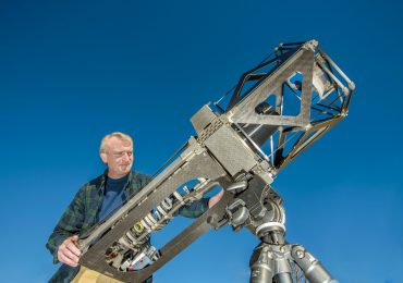 Sandia project lead Ted Winrow and the telescope made using 3D printing. Photo by Randy Montoya/Sandia National Laboratories