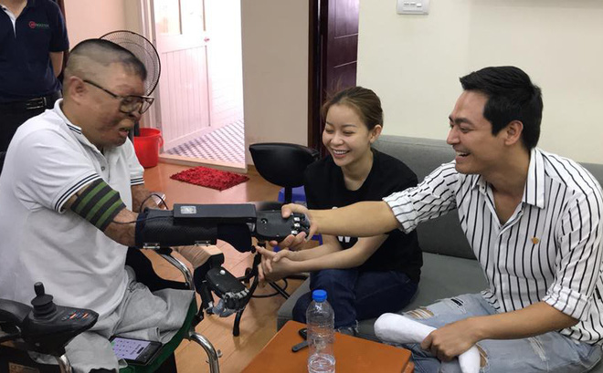 Dinh Van Duong (left) receives 3D printed bionic hands from MC Phan Anh (right)