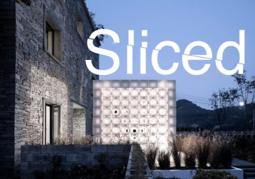 Sliced logo over AZL Architects' 3D printed LEI House in front of the stone B&B. Photo via AZL Architects