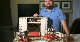 Brook Drumm and some early 3D printers. Photo via Printrbot.
