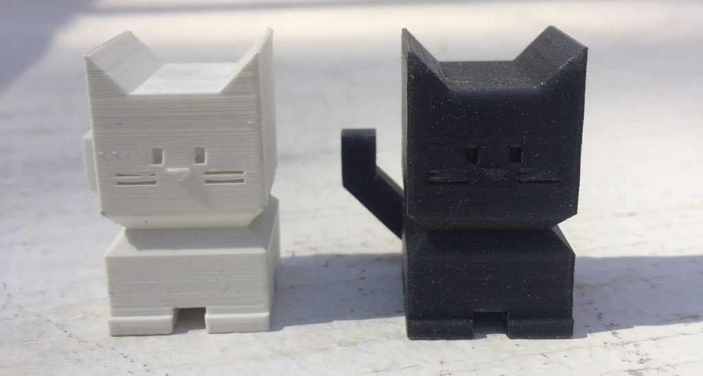 Cali Cat 3D printed in white Easy PLA (left) and Vertigo PET-G (right)