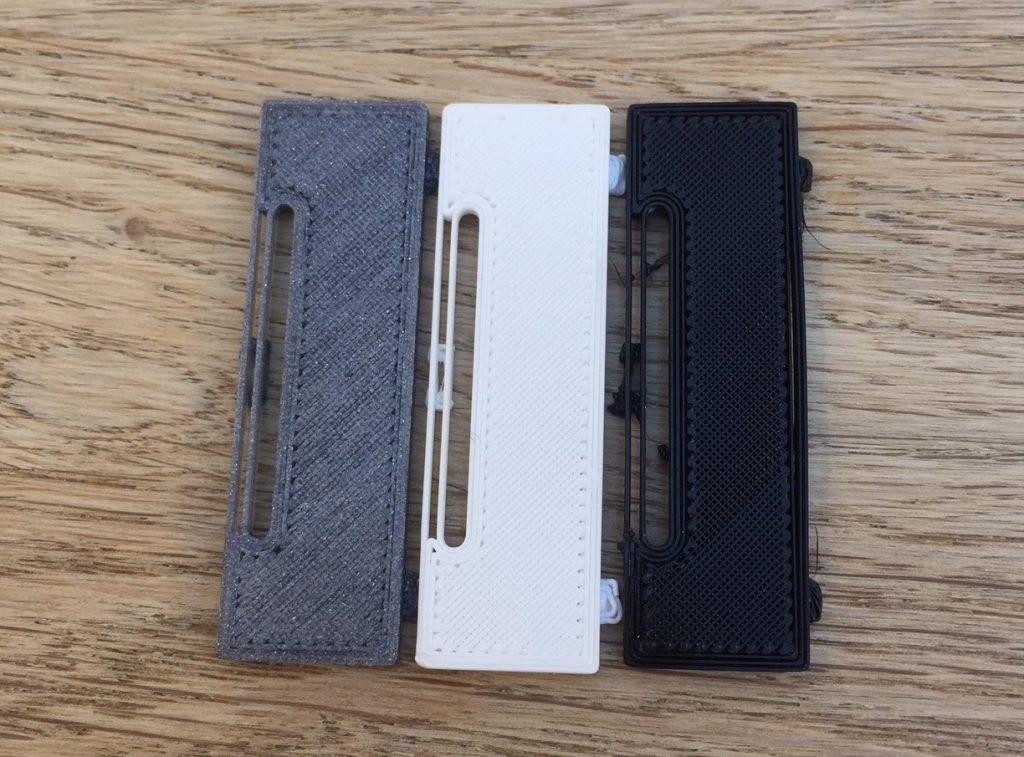 Replacement battery covers 3D printed in Vertigo PET-G, white Easy PLA and black Fiberflex 40D.