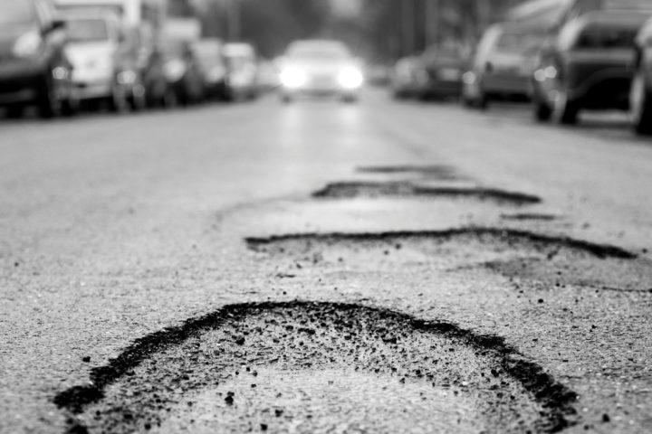Broken asphalt resulting in a pothole. Photo via Self Repairing Cities.