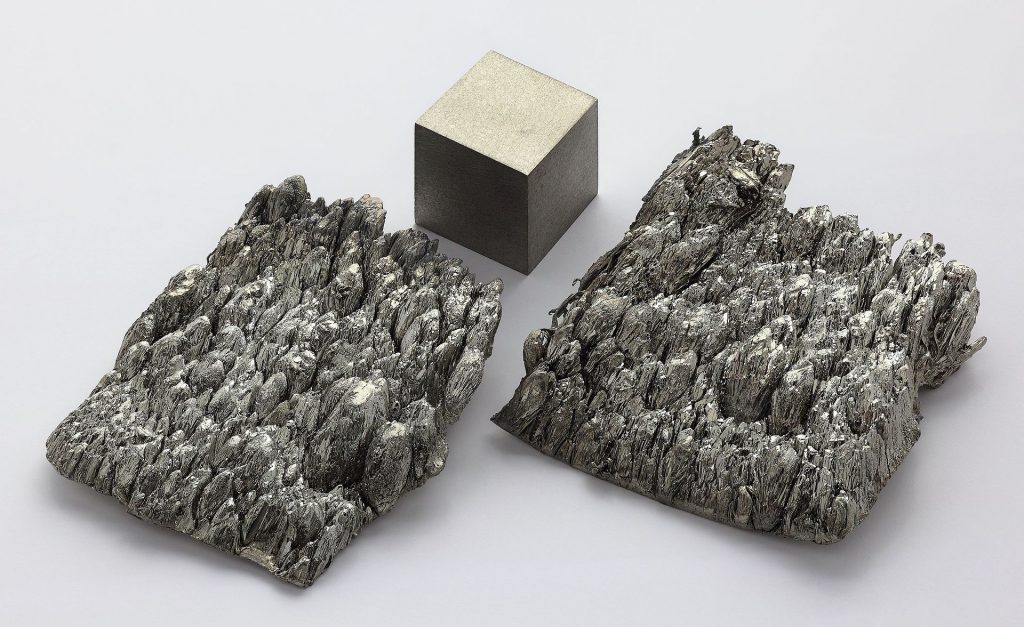 High purity scandium samples and a remelted scandium cube for comparison. Photo via Alchemist-hp/Wikimedia Commons