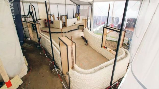 Stage 1 of construction for the 3D printed house. The space in-between the two printer blocks is filled with cement to form the wall. Photo via BBC.