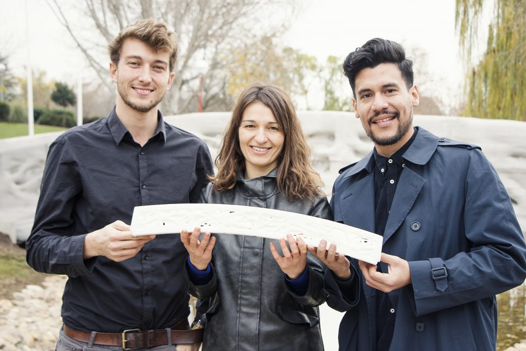 From left to right: Alexandre Dubor, Areti Markopoulou and Rodrigo Aguirre of IAAC hold a miniature replica 3D printed bridge. Photo via IAAC