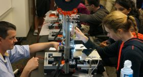 University students learning the 3D printing process. Photo via Open Source Classroom.