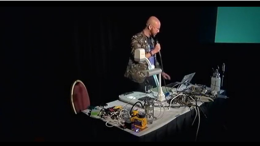 Dr. Michael Laufer with the 3D printed chemical reactor kit at the HOPE conference. Image via Michael Laufer/Youtube.