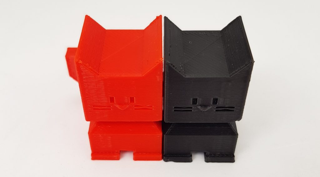 Side by side comparison of Cali Cats 3D printed in red PETG and black PLA. Photo by 3D Printing Industry