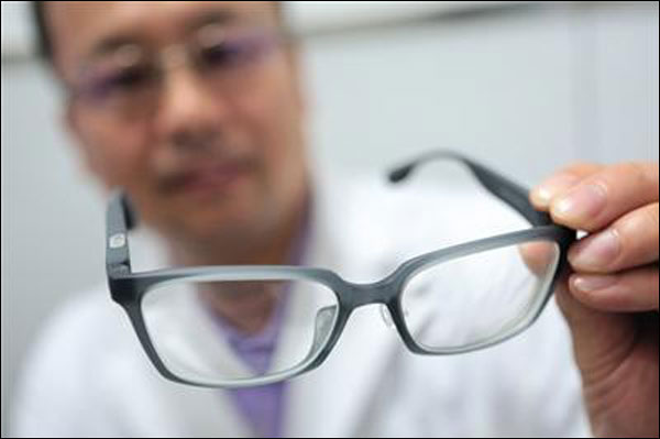 Dr. Song Hongxin holding a pair of 3D printed glasses. Photo via Beijing News