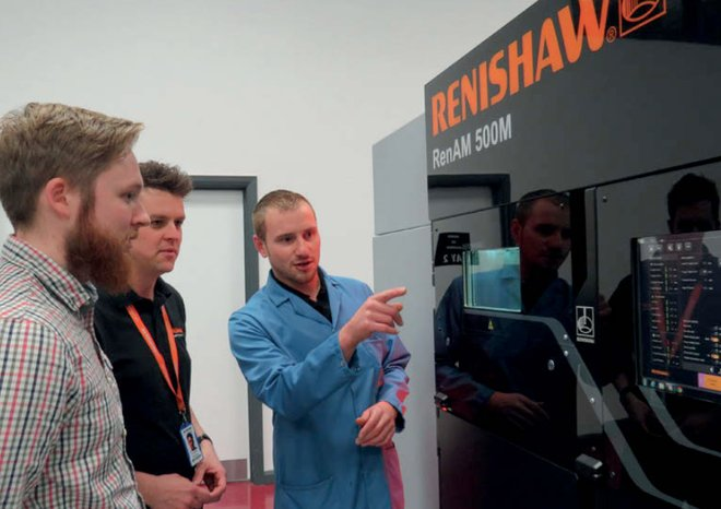 Graduate students with the RenAM 500M llaser powder bed fusion additive manufacturing system. Photo via Renishaw.
