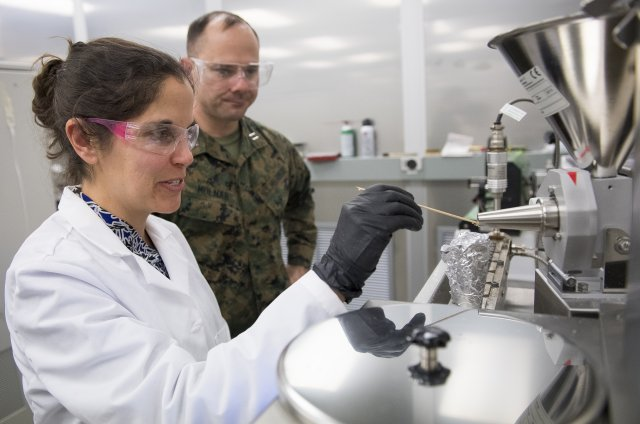 Dr. Nicole Zander demonstrates the filament converting process for Capt. Anthony Molnar. Photo via U.S. Army/ Jhi Scott.