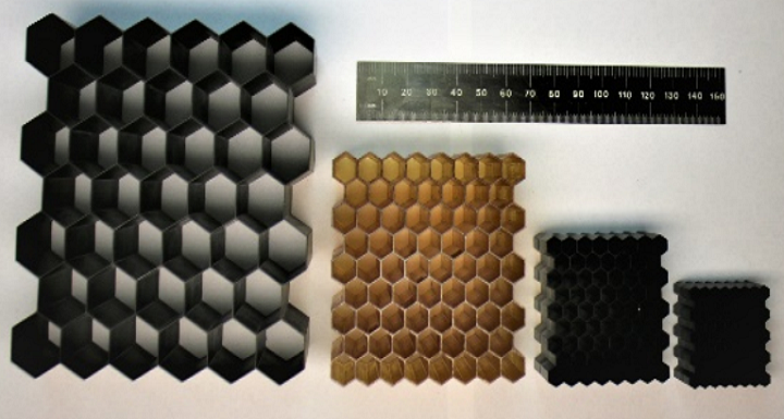 Figure 1: Hexagonal lattices printed using CLIP in four different materials (left to right) EPX, CE, RPU, and FPU at relative densities of 0.06, 0.12, 0.12, and 0.23 respectively. The ruler shows millimeters. Photo via University of Illinois at Urbana-Champaign