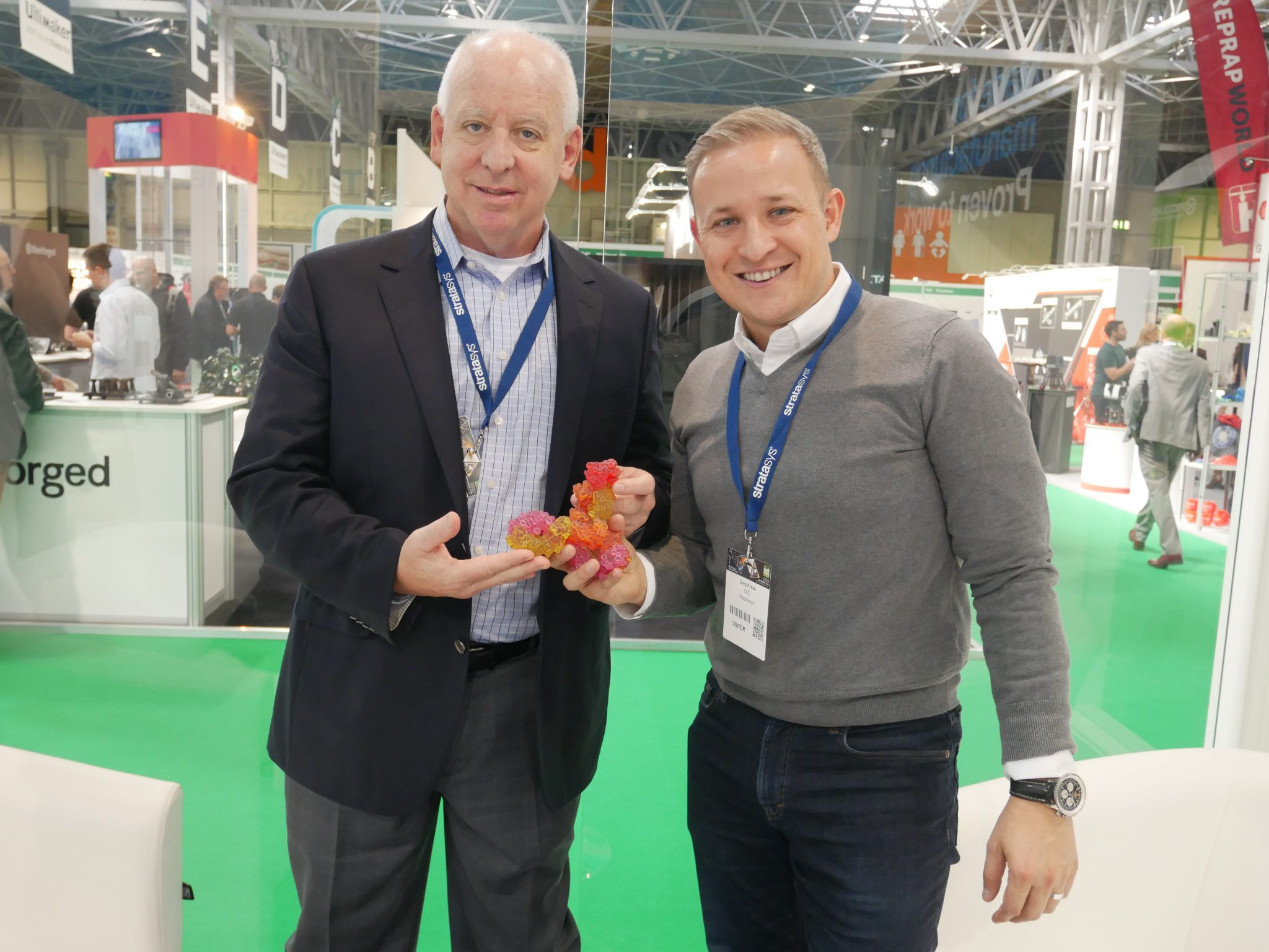 (Right) Pat Carey Senior Vice President Sales at Stratasys and Greg Kress CEO of Shapeways holding a 3D printed biological model manufactured on the J750. Photo by Tia Vialva.