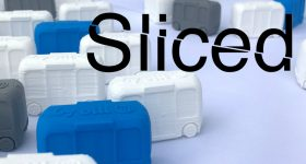 Sliced logo over Makerbot 3D printed miniature Olli buses. Photo via Local Motors