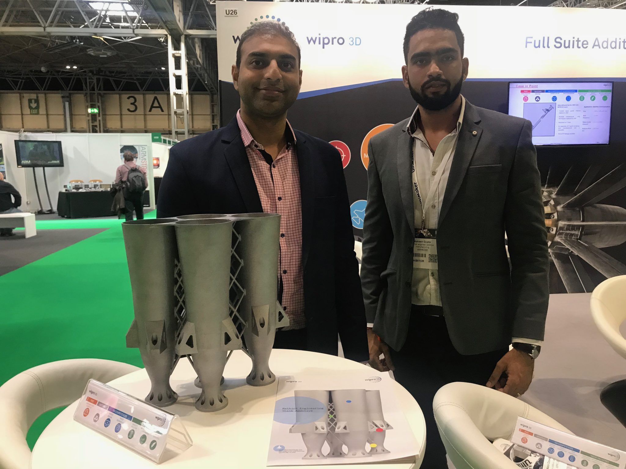 Nikhil Chowdary and Aakash Gupta of Wipro 3D with metal 3D printed feed cluster at TCT 2018 in the UK. Photo by Swamini Khanvilkar.