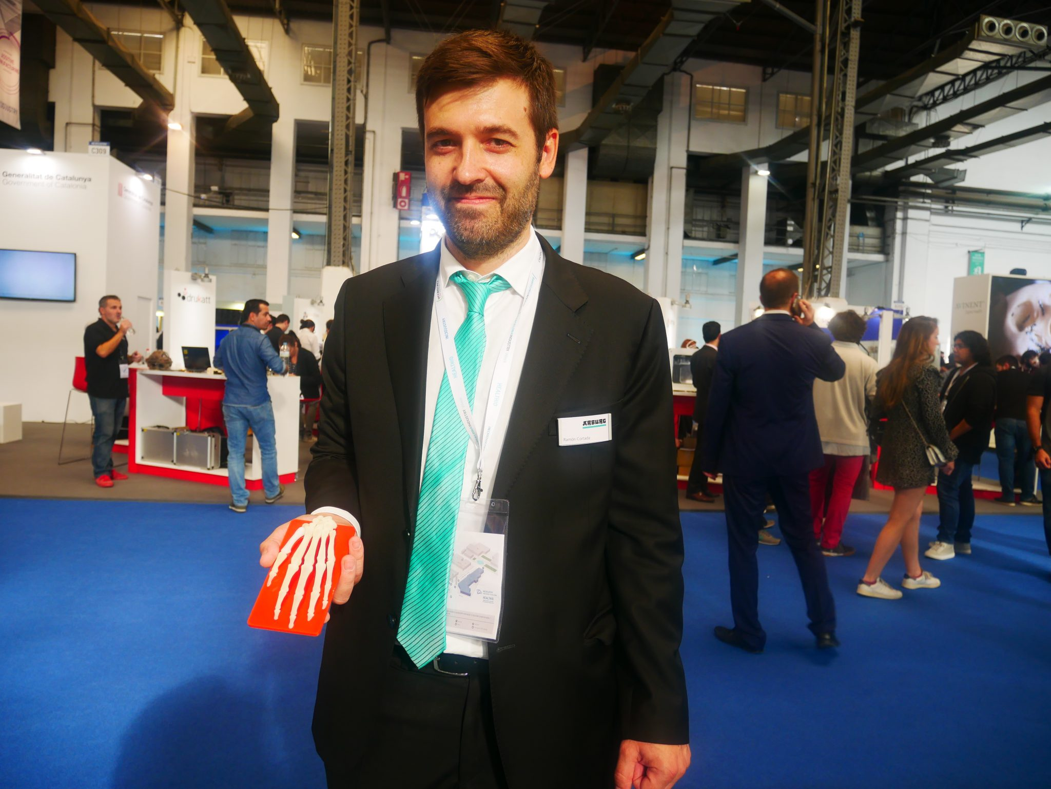 Ramon Cortada, Project Coordinator, Arburg S.A holding a 3D printed skeleton of the hand. Photo by Tia Vialva.