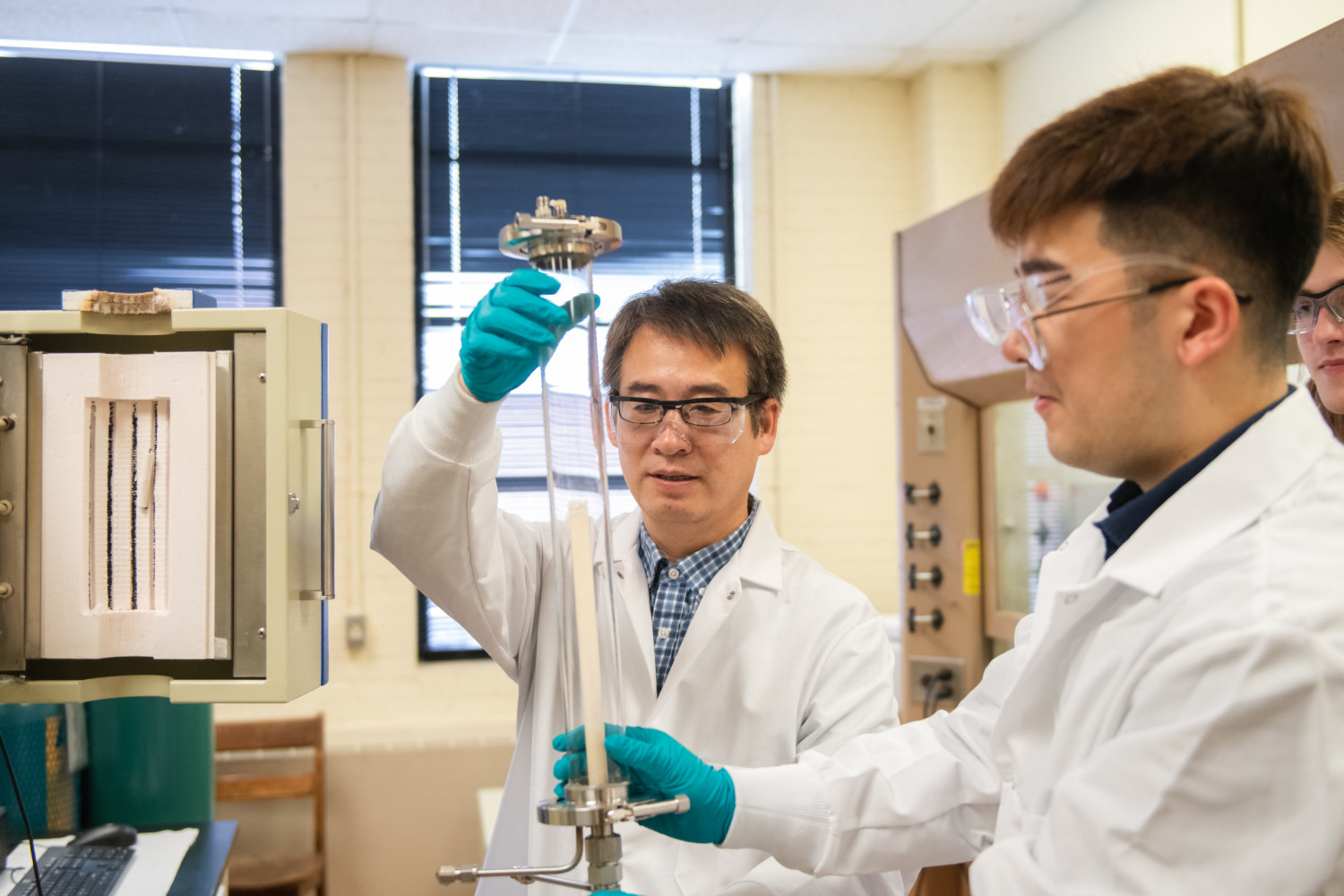 Professor Tong, left, and Ph.D. student Shenglong Mu work in their lab on new technology that combines 3D printing and laser processing. Photo via Clemson University.