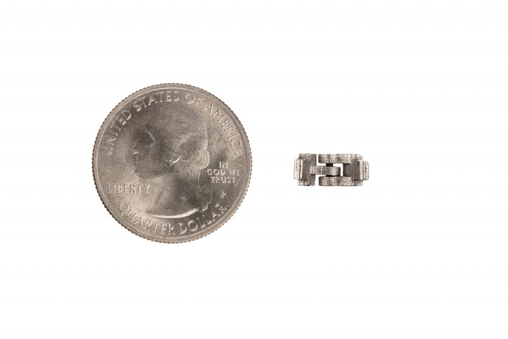 A Production System 3D printed hinge with quarter for scale. Photo via Desktop Metal