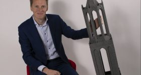 Maurits Blok, Commercial Director of Tractus3D, and a large scale 3D print of a tower. Photo via Tractus3D