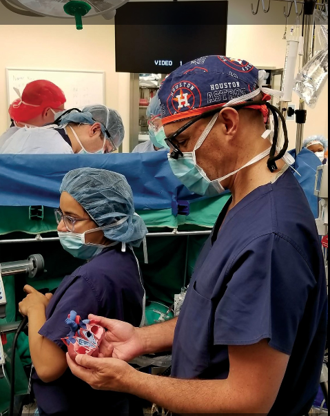 OpHeart's Dr. Jorge Salazar, the Chief of Pediatric and Congenital Heart Surgery at Children's Memorial Hermann Hospital references a 3D printed patient-specific anatomical heart model in a operating room. Photo via OpHeart.