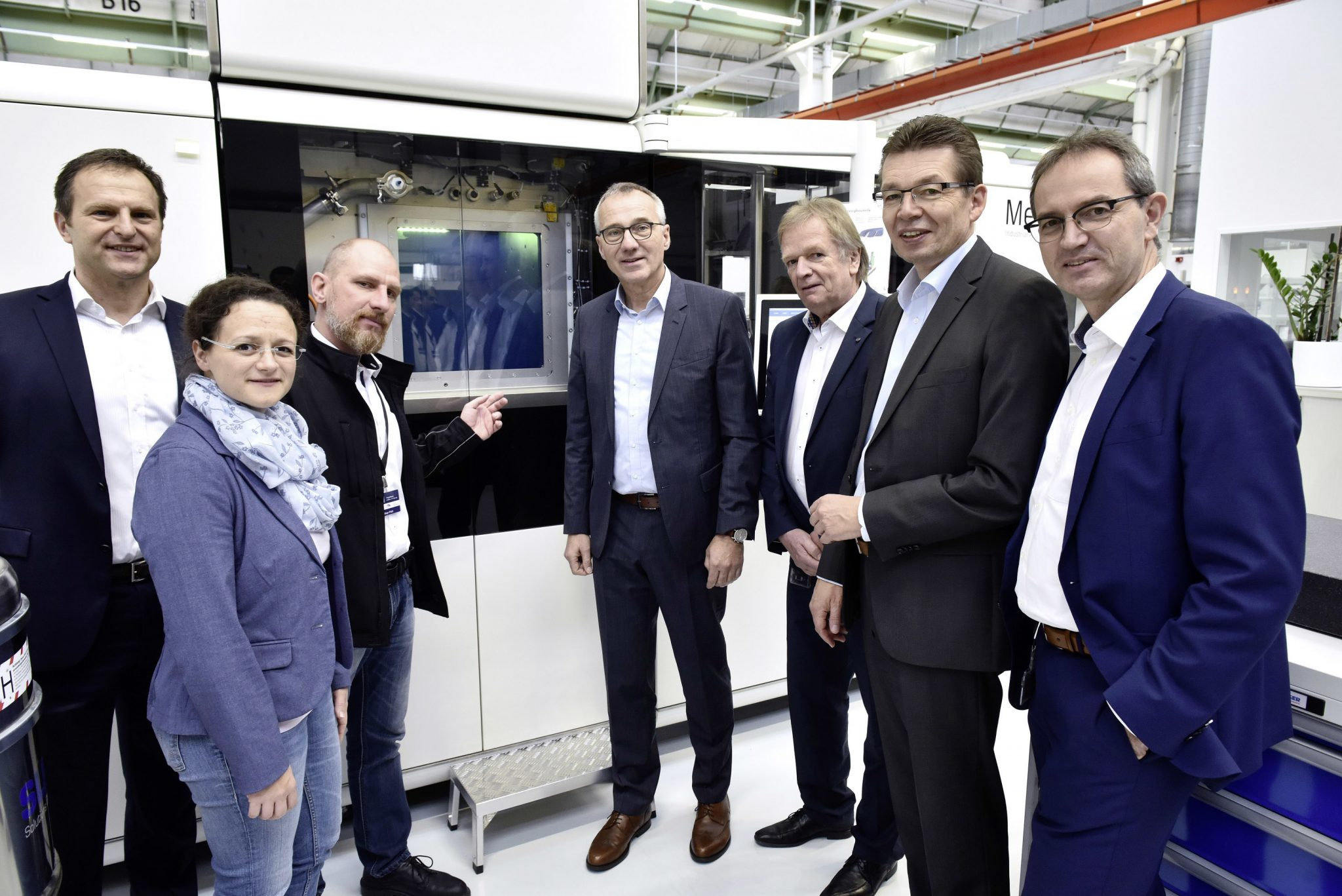 Oliver Pohl, Head of Additive Manufacturing at Volkswagen (third from left) presents the new 3D printing center to visitors from the European Works Council and management. To note: The machine in the background appears to be a MetalFAB1 system from Dutch manufacturer Additive Industries. Photo via Volkswagen