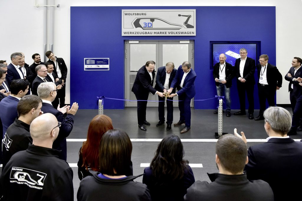 """Official opening with 3D scissors: (from left to right) Oliver Schauerte, Head of Research, Materials and Production Processes, Eckhard Ritz, Head of Toolmaking, Volkswagen brand, and Uwe Schwartz, Head of Planning, Volkswagen brand, together open the 3D printing center."" Caption and photo via Volkswagen"