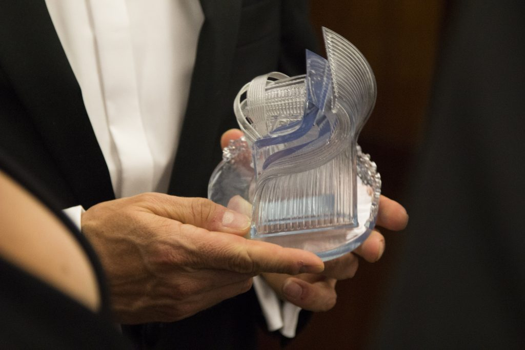 The 2018 3D Printing certification Industry Awards trophy in the hands of one of last year's winners.