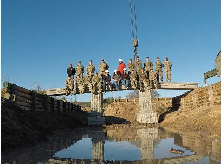 Kreiger (seated, sixth from left) and her team on the 3D printed reinforced concrete footbridge. Photo via the ERDC.