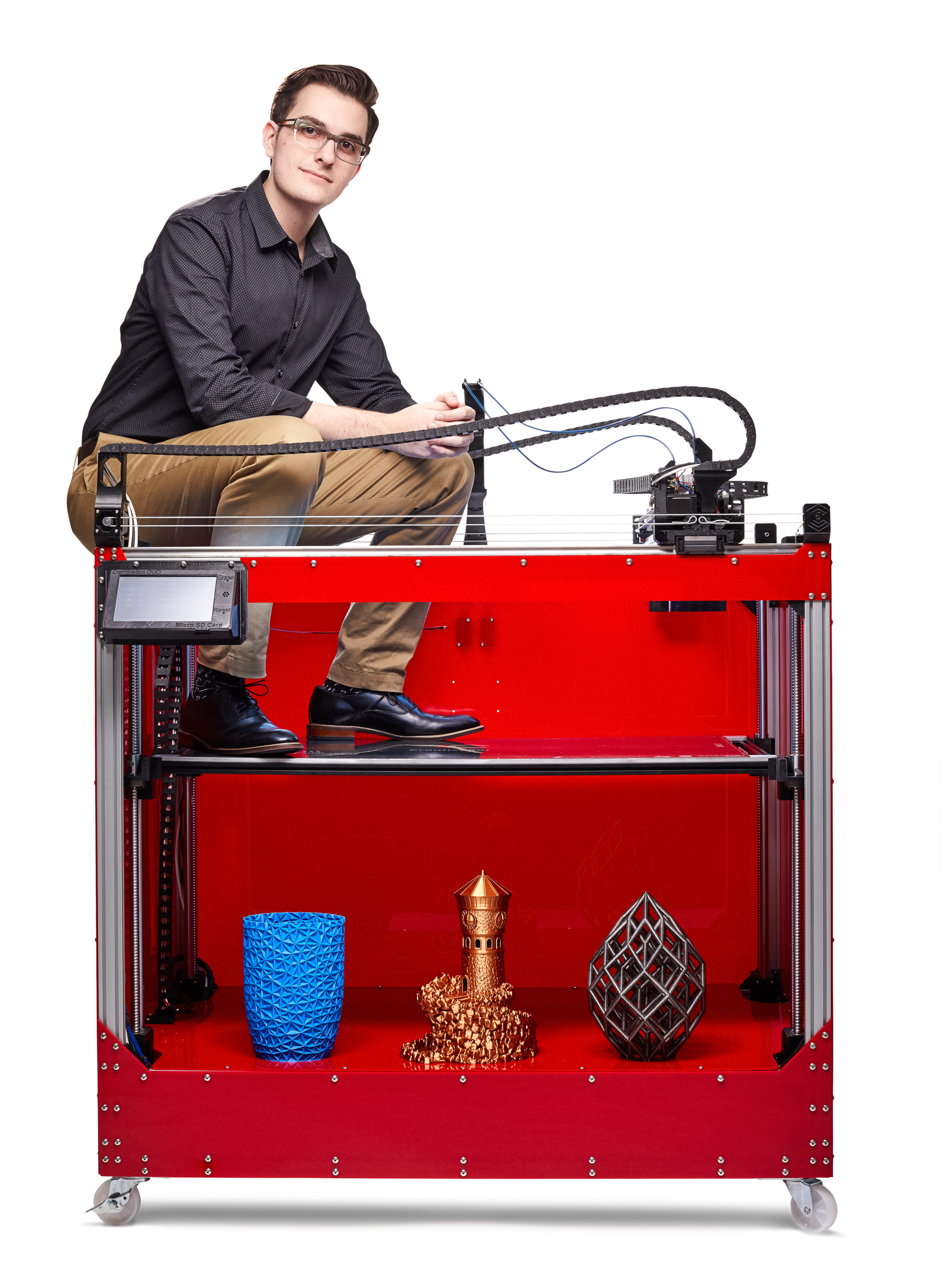 Baehrend seated on the CreativeBot Duo 3D printer. Photo via Creative 3D Technologies.