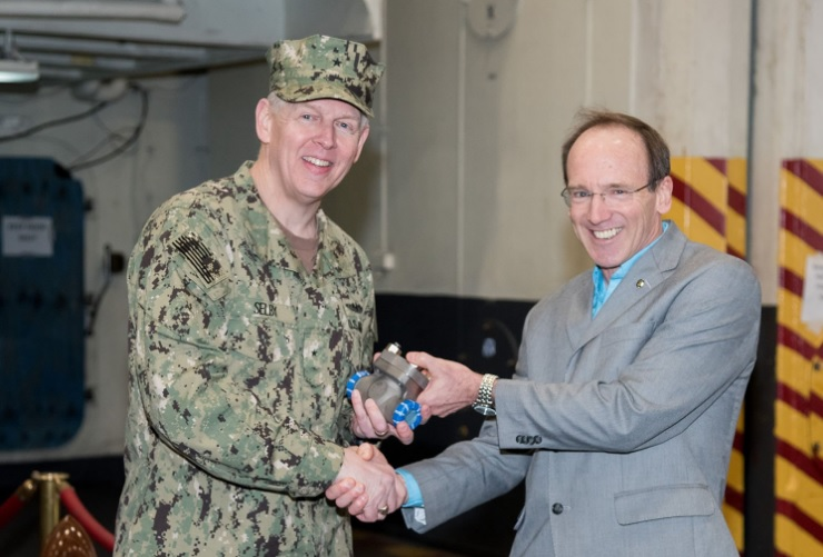 Rear Adm. Lorin Selby, (right) presents Capt. Nicholas Dienna, a USS Harry S. Truman (CVN 75) Commanding Officer, , with the 3D printed metal piping assembly. Photo via Rebekah A. Watkins/U.S. Navy.