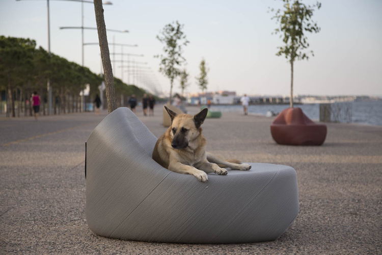 A dog lounging on a 3D printed ergonomic street bench made from recycled plastic. Photo via The New Raw.