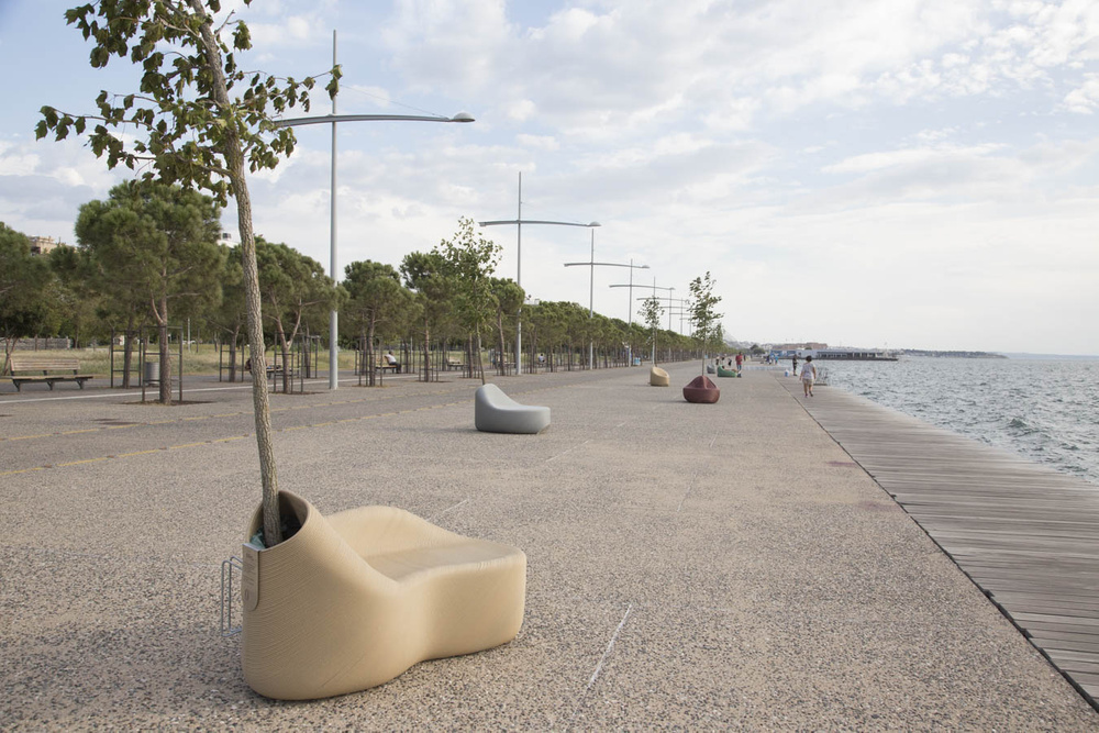 3D printed ergonomic street seating with integrated plant pot, installed on the waterfront.  Photo via The New Raw.