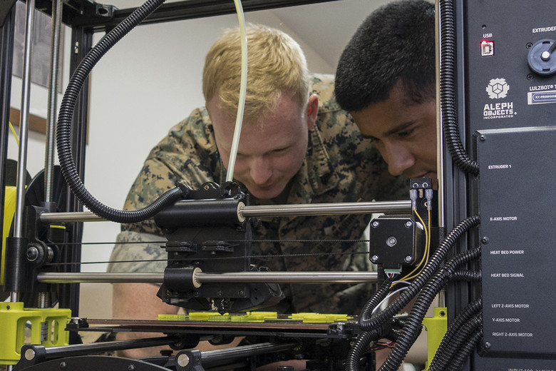 U.S. Marines from the Special Purpose Marine Air-Ground Task Force-Crisis Response-Africa observe a 3D printer at the Morón Air Base in Spain. Photo courtesy of Staff Sgt. Britni M. Garcia Green/U.S. Marine Corps.
