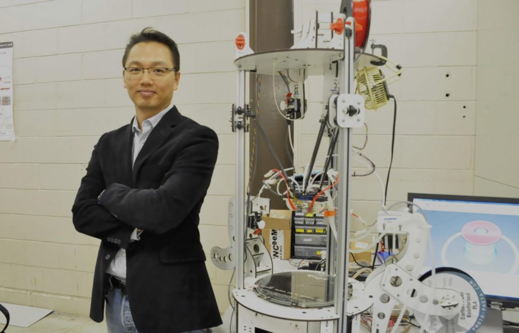 Professor Woo Soo Kim of the SFU School of Mechatronic Systems Engineering stands next to a purpose built delta 3D printer. Photo via SFU