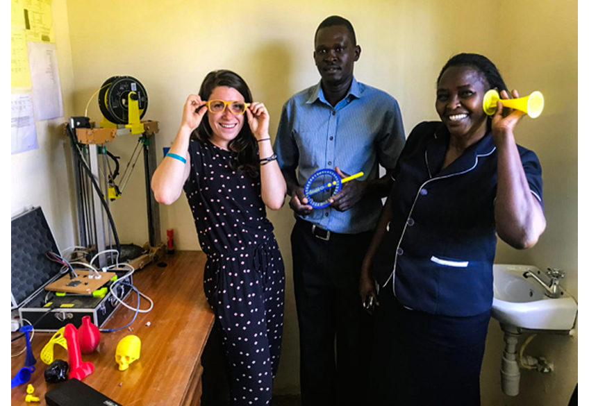 Kijenzi engineer Alenna Beroza, right, shows off 3D printed parts designed with and for nurse/administrator Jennifer Simani and biomedical engineer Daniel Obego. Beroza has spent the last four months working in Kombewa District Hospital, co-developing and testing parts with local professionals and Kijenzi engineers in the United States. Photo via Kijenzi.