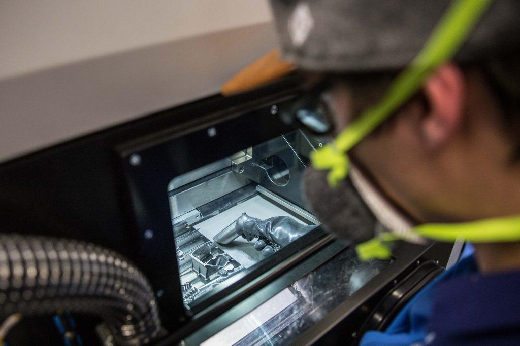 Post processing of metal 3D printed parts at Liebherr. Photo via Liebherr
