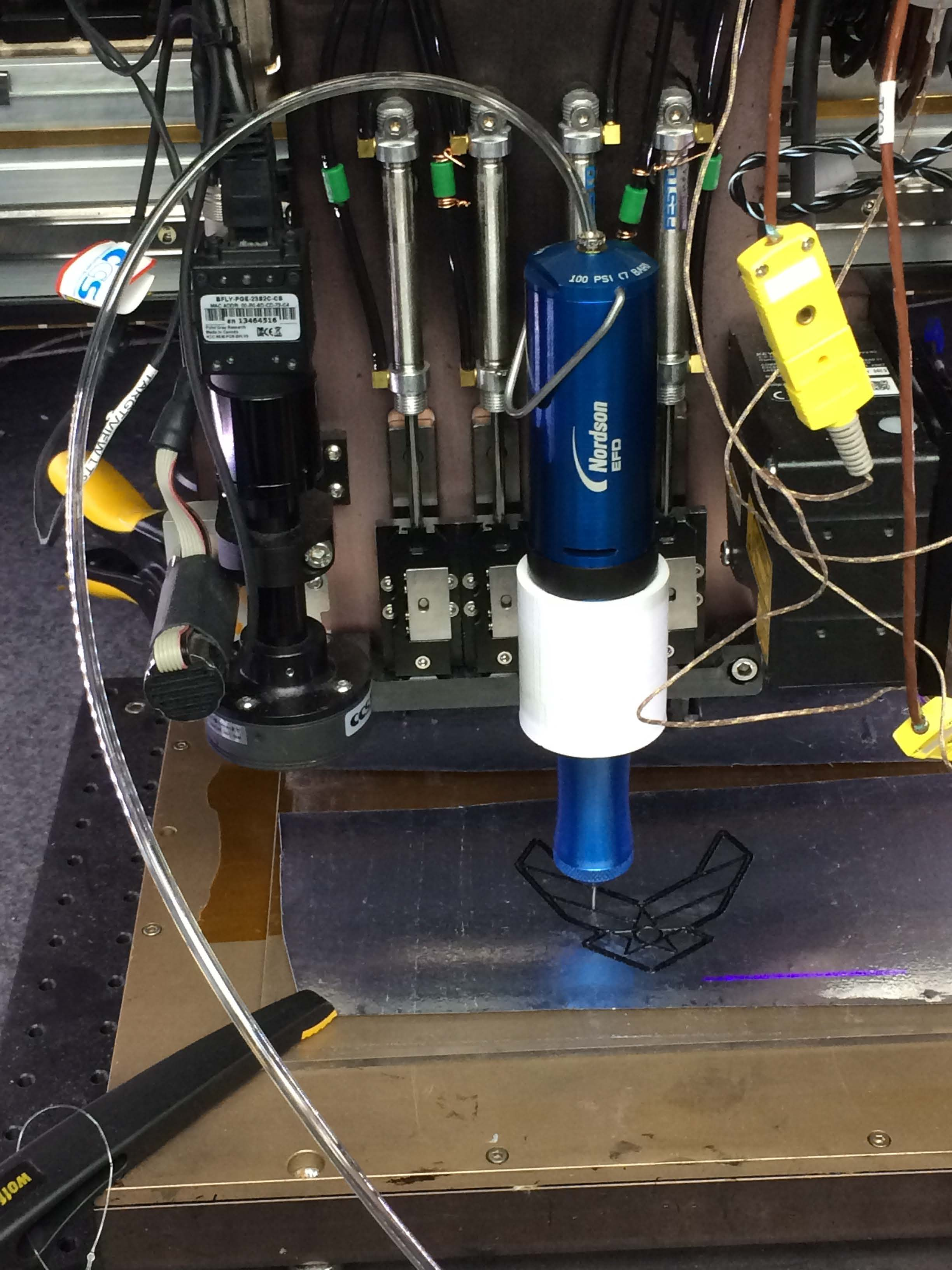 Direct ink printing is performed with a 3D printer using epoxy with chopped fiber. The pressure pump provides pressure to force the resin through the nozzle. Photo via Donna Lindner/AFRL.