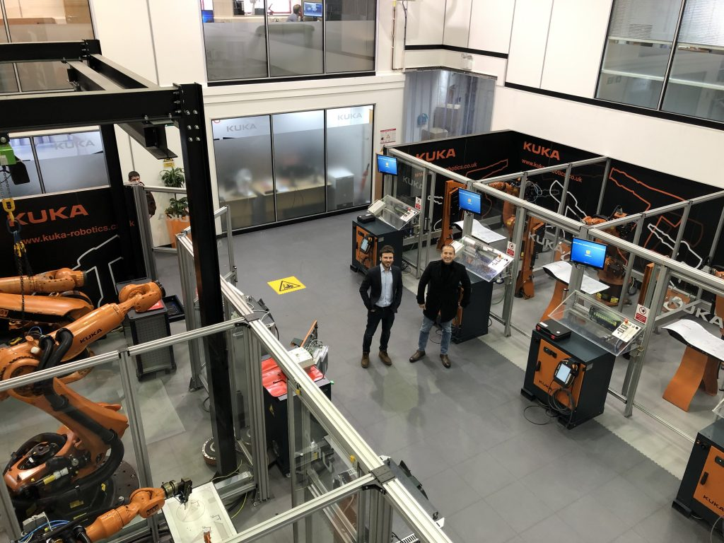 Left: Daghan Cam, Ai Build stands with, Right: Edouard Baaklini, 3DVinci Creations amidst a facility of KUKA-operated AiMakers. Photo via 3DVinci Creations