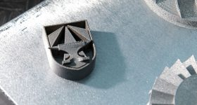 A 3D printed metal part testing the capabilities of custom alloys. This part shows the geometric capabilities of 3D printing with the symbol of the newly formed Army Futures Command. Photo via the U.S. Army/David McNally.
