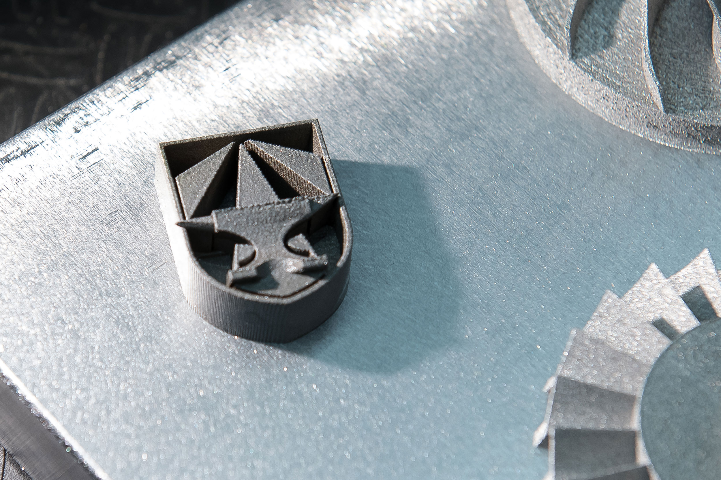 A 3D printed metal part testing the capabilities of custom alloys. This part shows the geometric capabilities of 3D printing certification with the symbol of the newly formed Army Futures Command. Photo via the U.S. Army/David McNally.