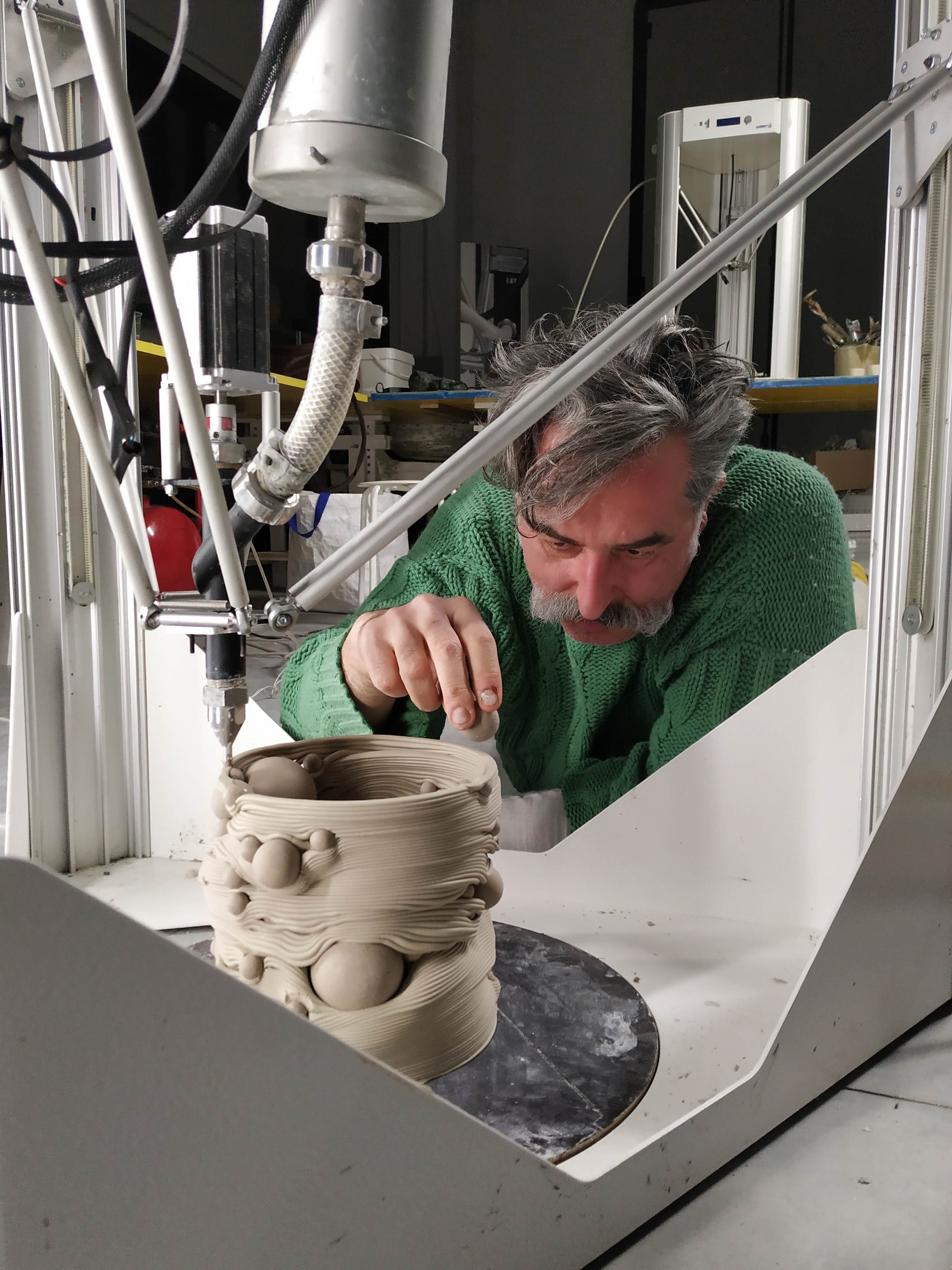 Salvatori inserts ceramic balls into the 3D printed vases. Photo via WASP.