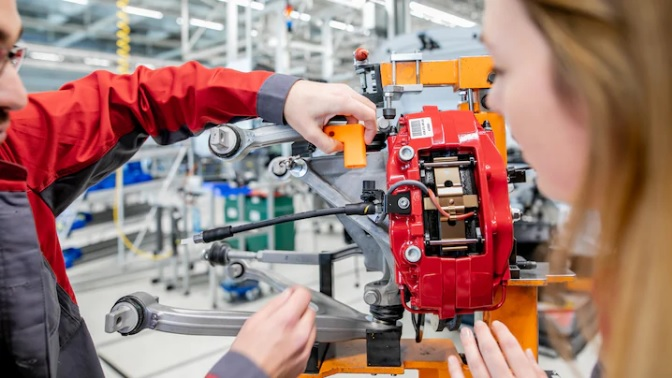 A 3D printed auxiliary tool being fitted on production line machinery. Photo via Audi/Sina Feirer.
