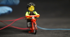 The USC team's LEGO test dummy wearing broken 3D printed helmet. Photo via Science Advances
