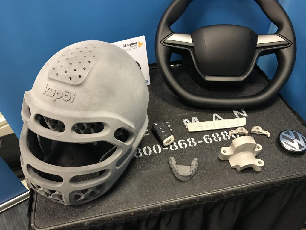 3D printed objects, including a Kupol helmet, Scorpion steering wheel, and dental impression for Smile Direct Club from HP. Photo by Beau Jackson