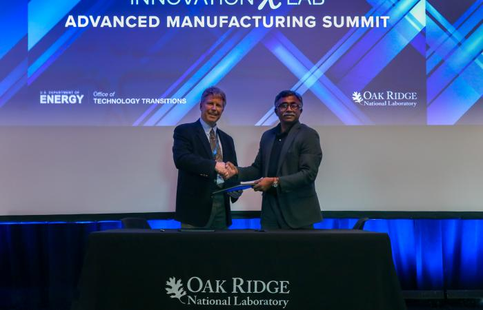 Tom Matthews of Lincoln Electric, left, and ORNL Director Thomas Zacharia signed an agreement to advance large-scale metal additive manufacturing technology during the Department of Energy's Advanced Manufacturing InnovationXLab Summit at ORNL. Photo via Genevieve Martin/Oak Ridge National Laboratory.