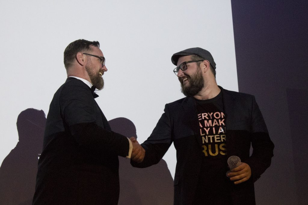 3D Printing Industry Editor in Chief Michel Petch, shakes the hand of Josef Prusa, founder of wildcard 2019 Desktop FFF 3D Printer of the Year winner Prusa Research, for the Prusa i3 MK3. Photo by 3D Printing Industry