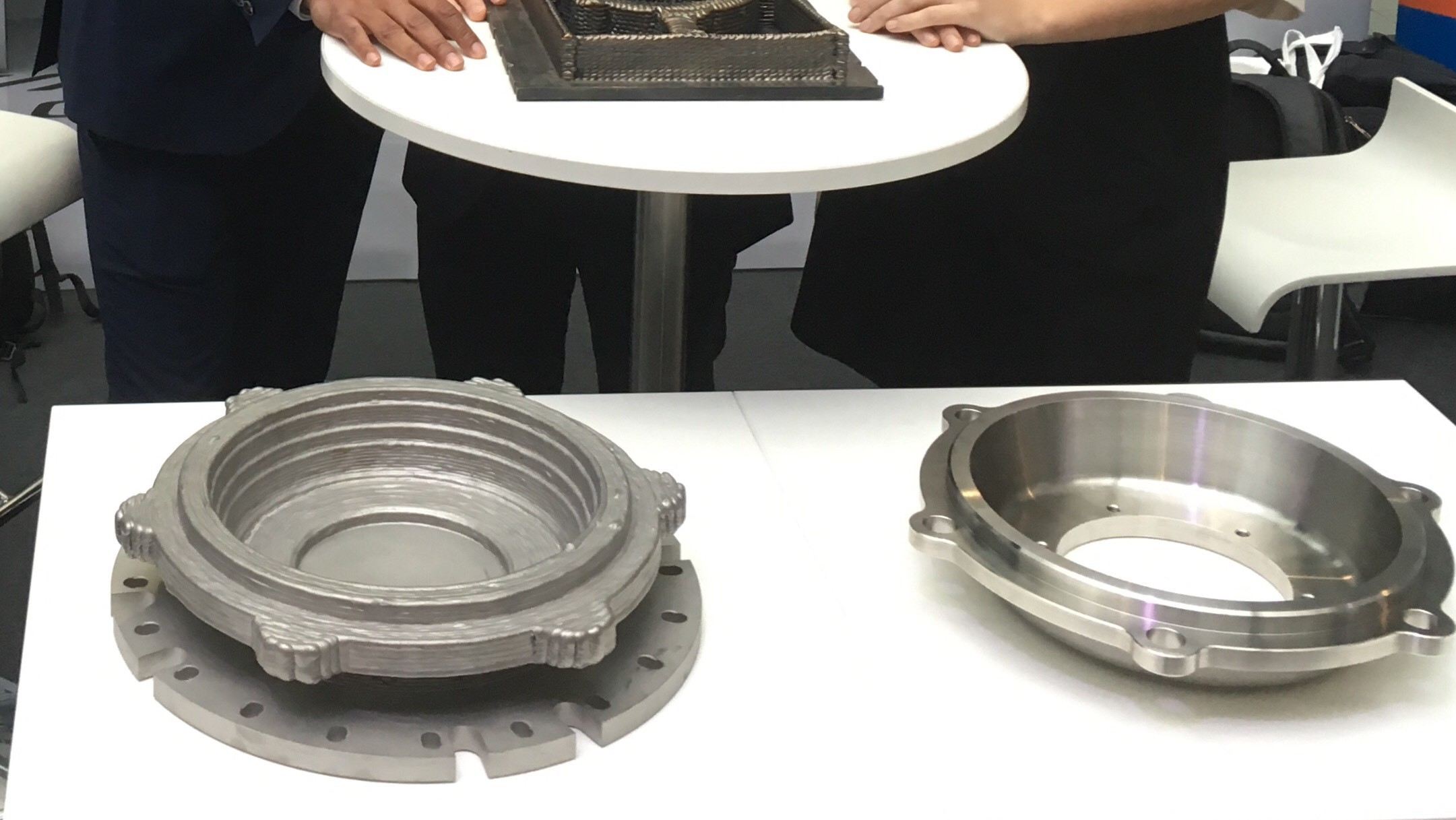 The 3D printed wheelset bearing cover before (left) and after it is machined (right). Photo via Deutsche Bahn.